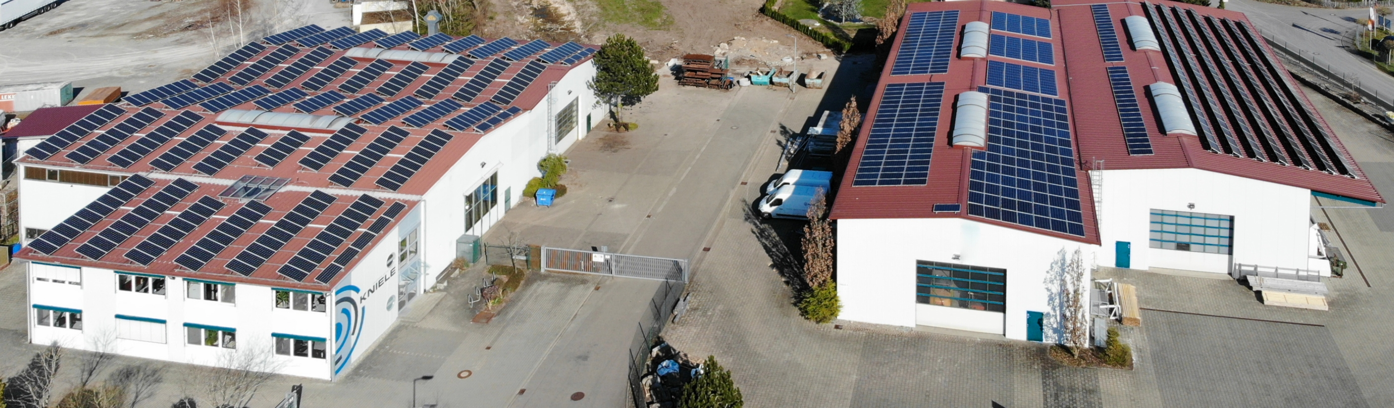 Bird's eye view of Kniele's production halls with PV system on the roof, Kniele logo at the administration building.