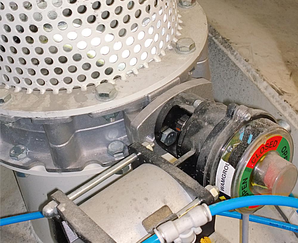 Gerundetes Lochblech angeflanscht auf einer Drehklappe mit Getriebe und Motor und blauen Pneumatikschlaeuchen.