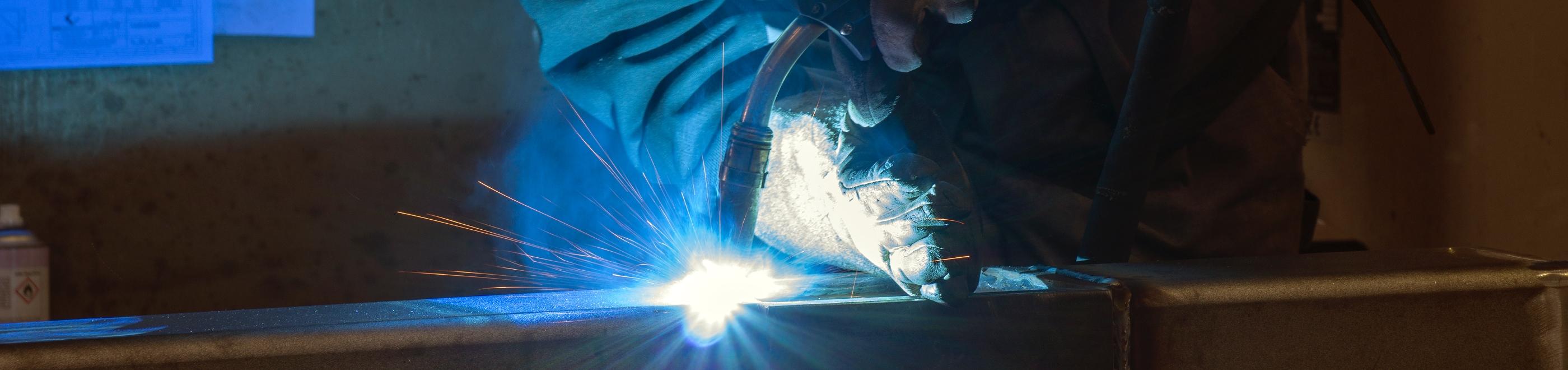Schweisser beim Schweissen eines Metalltraegers mit Lichtbogen.
