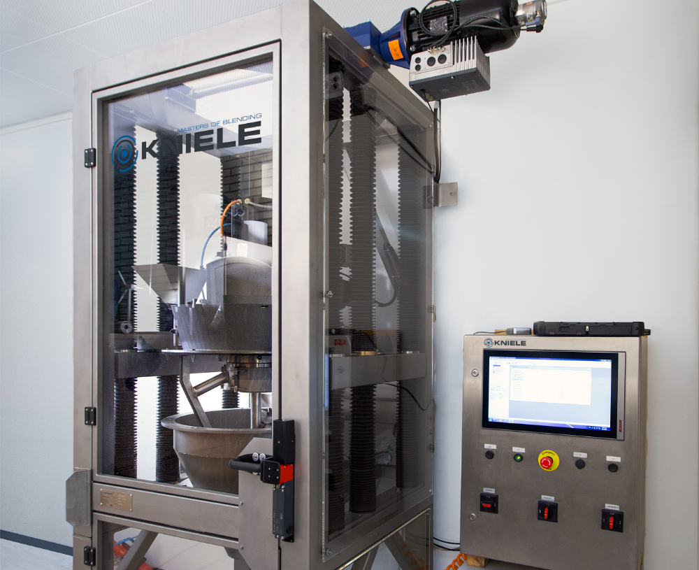 Stainless steel frame with a conical mixer behind plexiglass and a control box to the right.
