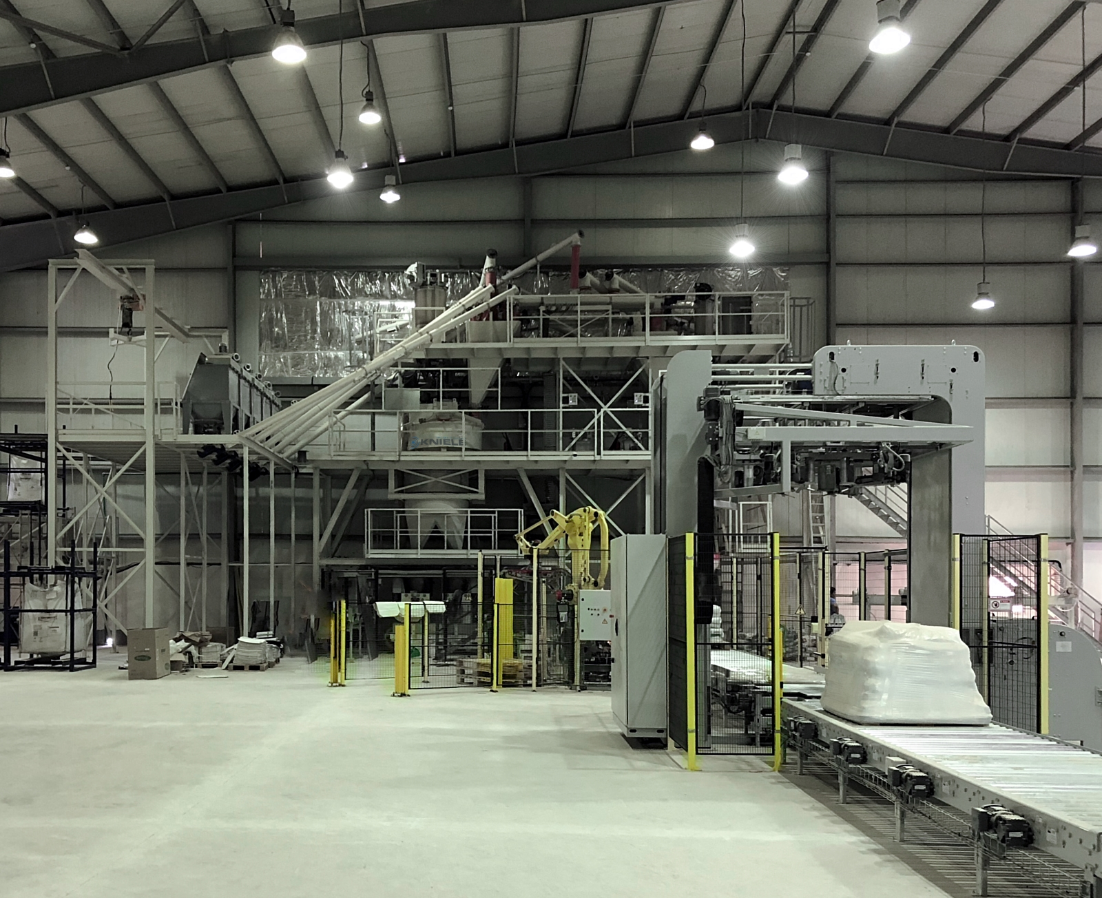 White concrete mixing plant over two levels in a brightly lit hall with concrete mixer and cement screws and packaging machine in the foreground.