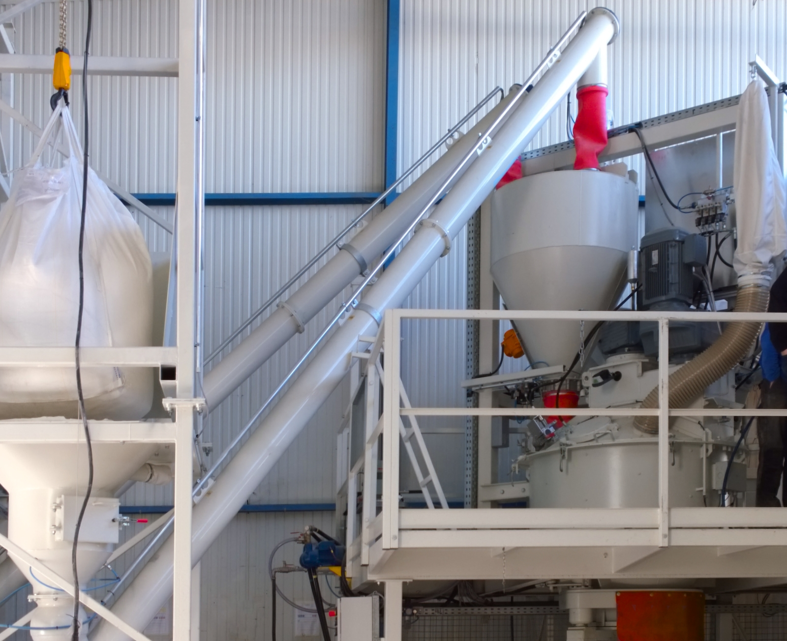 White concrete mixer with cement scales above on a steel platform, with cement screws and a big bag station.