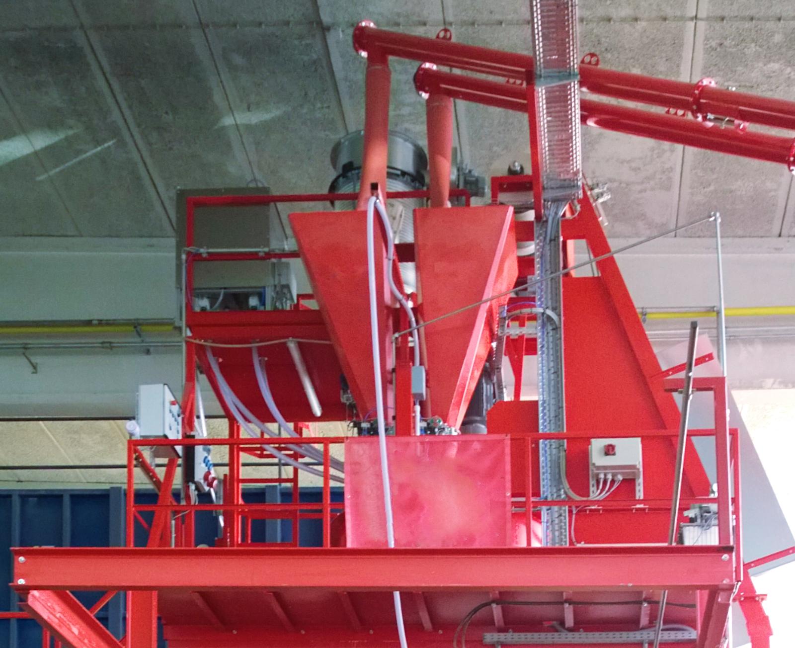 Plate-forme pour malaxeur rouge avec balance à ciment, skip et vis à ciment de la droite.